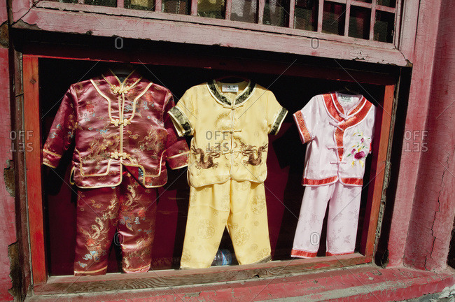 Three children's outfits in a display case in an open window, Forbidden City, Beijing, China
