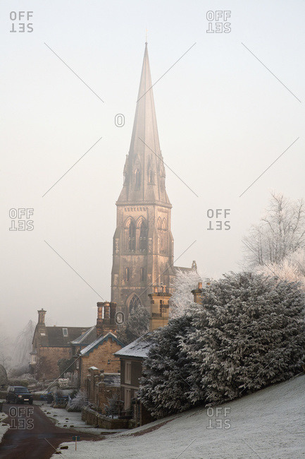 Tall steeple of a church in the fog on a frosty morning, Edendor, Derbyshire, England
