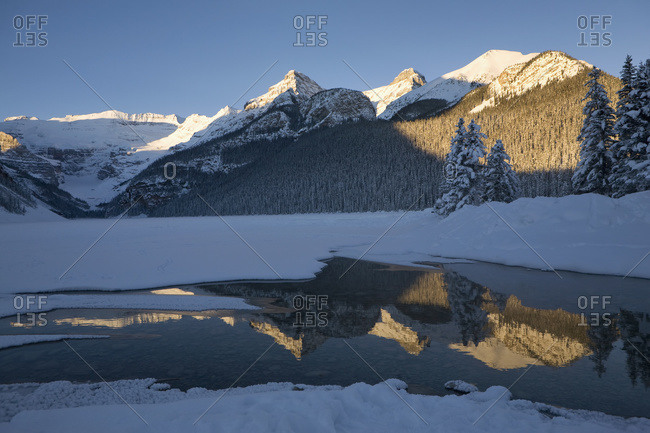 Early morning sunlit snow covered mountains reflecting in a lake with deep blue sky, Lake Louise, Alberta, Canada