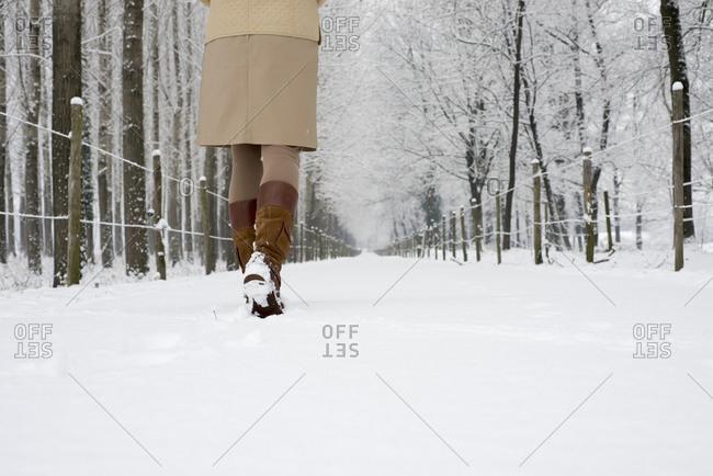 A woman walks down a snowy path in winter, Locarno, Ticino, Switzerland