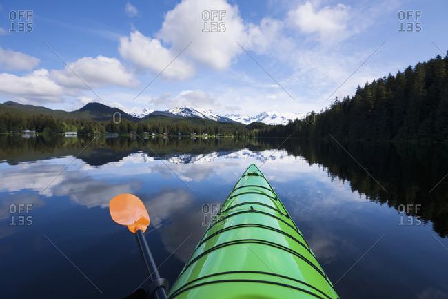 A kayaker enjoys a tranquil morning paddle on Auke Lake, Alaska, United States Of America