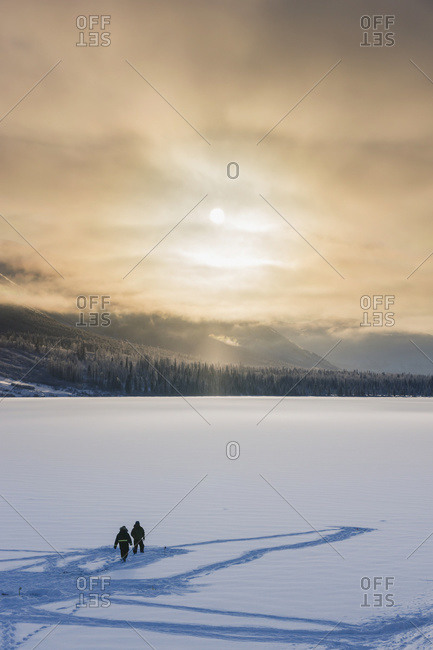 Silhouetted Ice Fisherman On Summit Lake, Clouds Clearing From The Kenai Mountains Behind The Lake, Chugach National Forest, Backlit Sun, Winter, Alaska, United States Of America