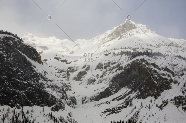 Snow covered mountains with the sun highlighting the peaks and a hazy blue sky, Alberta, Canada