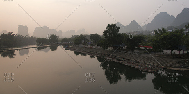 Houses along the waters edge with rugged mountain peaks in the background