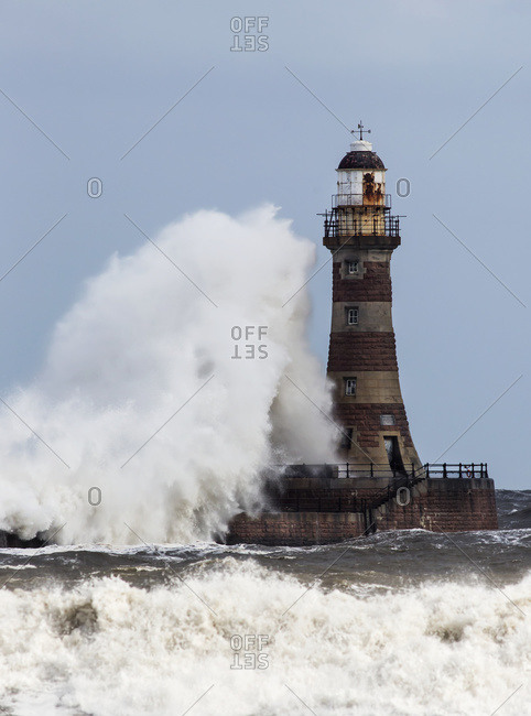 A large wave crashing into a lighthouse, Sunderland, Tyne And Wear, England