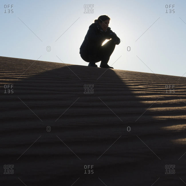 A woman crouching on the top of a sand dune, Souss-massa-draa, Morocco