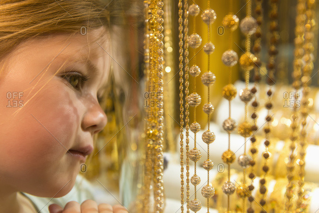 Young girl looking at gold jewelry for sale in window of shop in the gold souk, Dubai, United Arab Emirates