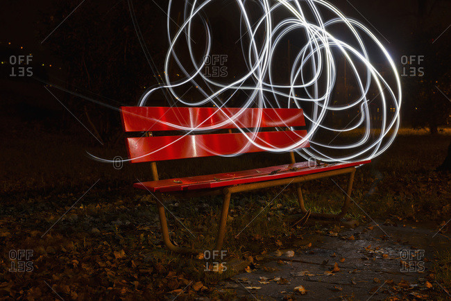 A red park bench in autumn with swirls of white light around it, Locarno, Ticino, Switzerland