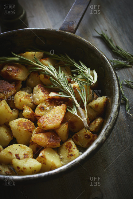 Crunchy potatoes with rosemary in an old iron pan