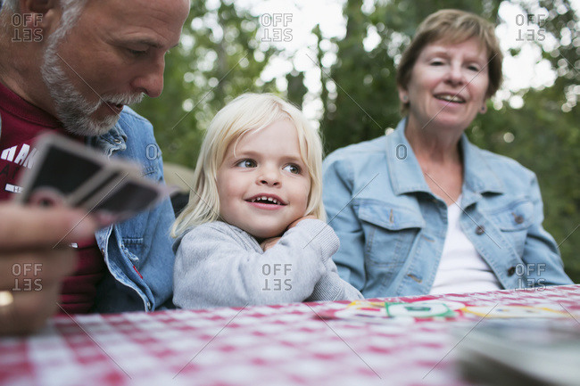 Grandparents playing a card game with a young granddaughter, Peachland, British Columbia, Canada