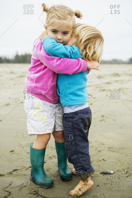 Young girl and boy have a warm hug and cuddle on the beach in summer, Tofino, British Columbia, Canada