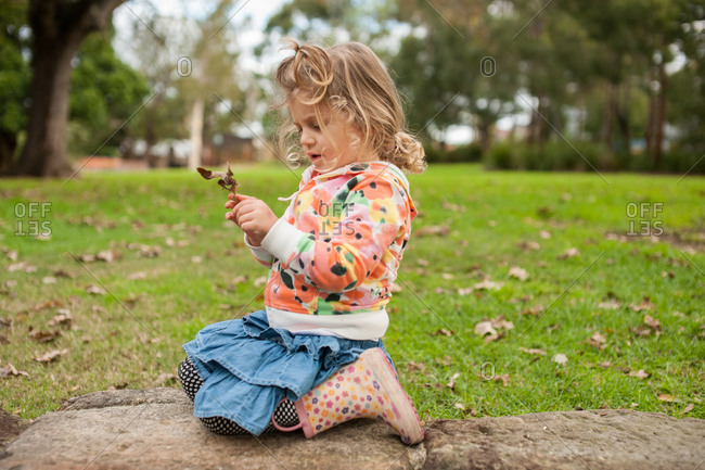 A little girl in rain boots picks up a leaf