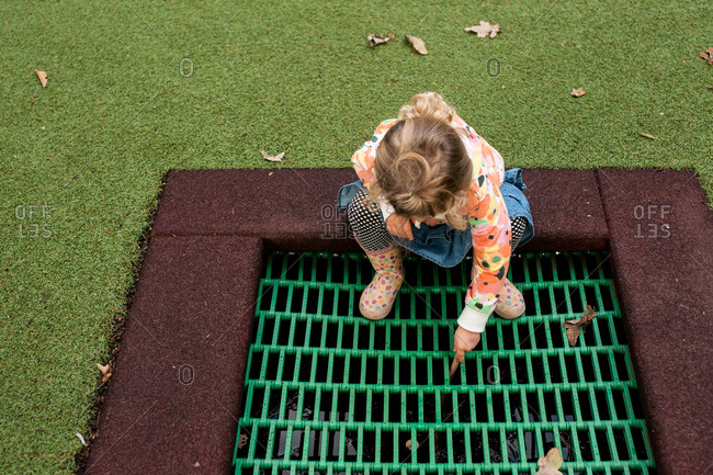A little girl in rain boots looks down a grate