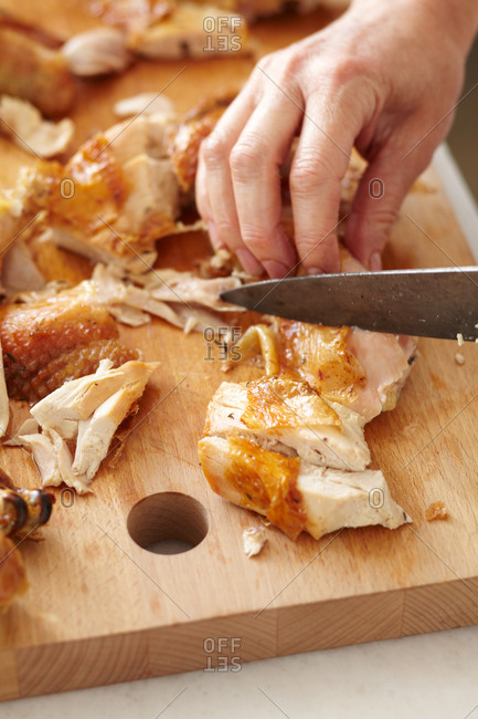 Woman slicing pieces of a whole roasted chicken