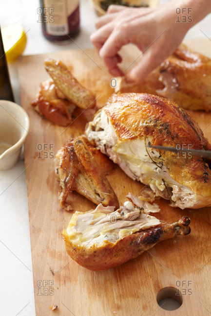 Woman cutting up a whole roasted chicken