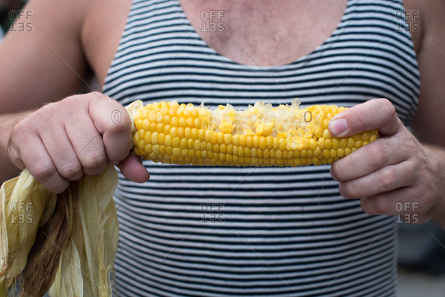 Close up of man in striped tank top holding a cooked ear of corn