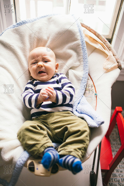 Discontented infant boy in bouncy seat