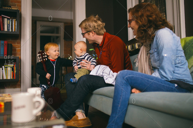 Parents and two young children enjoy time together in their living room