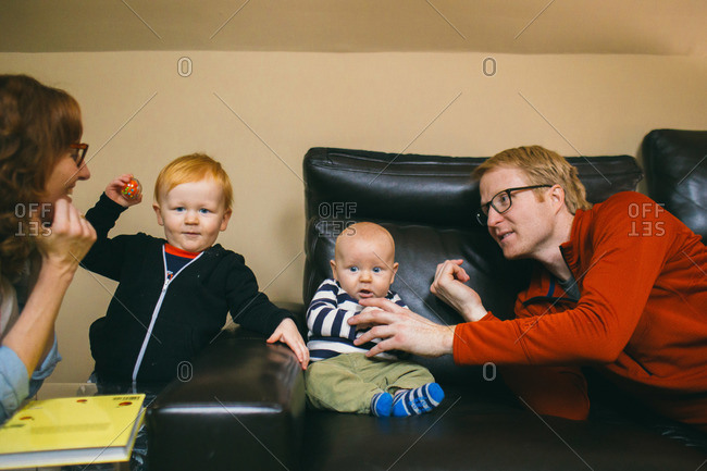 Parents and two young sons play near black leather couch