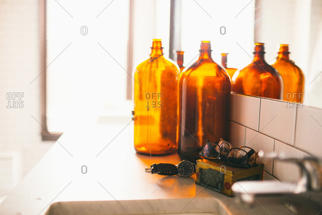 Antique glass bottles on counter next to watches and eyeglasses on retro- modern bathroom counter