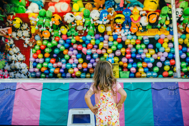 Girl looking at prizes to win at a fair