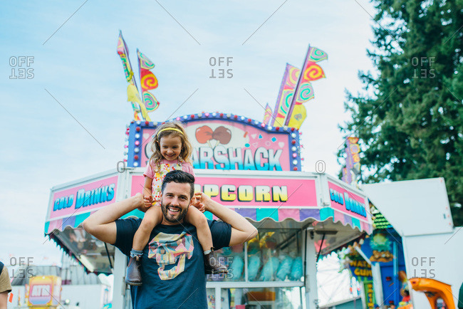 Girl riding on her dad's shoulders at a fair