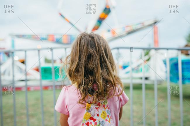 Girl watching an amusement ride at a fair