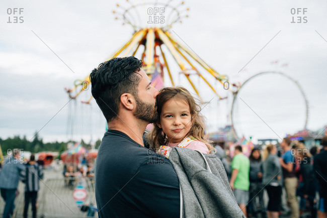 Father carrying his daughter at a fair