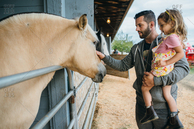 Father and daughter visiting petting zoo at a fair