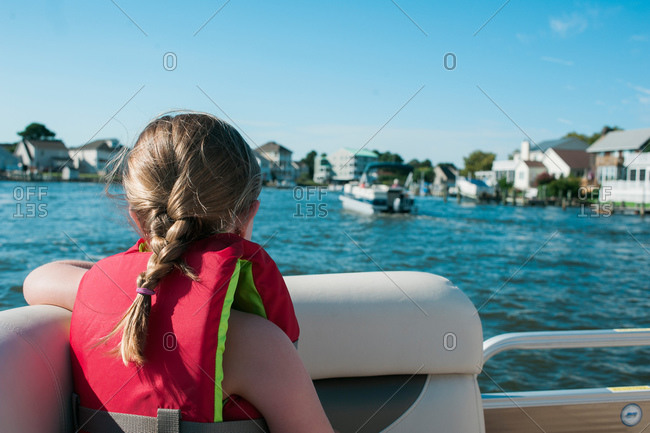 A young girl looks onto a lake from a boat