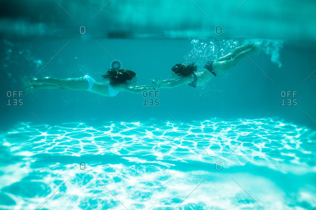 Two girls hold hands underwater in a pool
