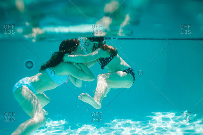 Two girls hug under water in a pool