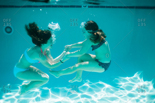 Two girls laugh and hold hands under water
