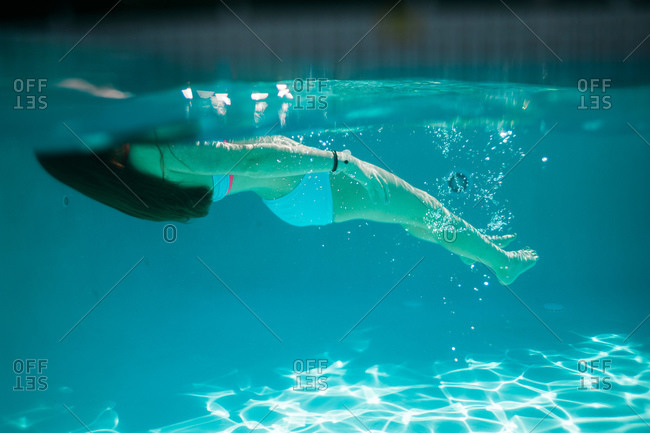 A girl floats on her back in a pool