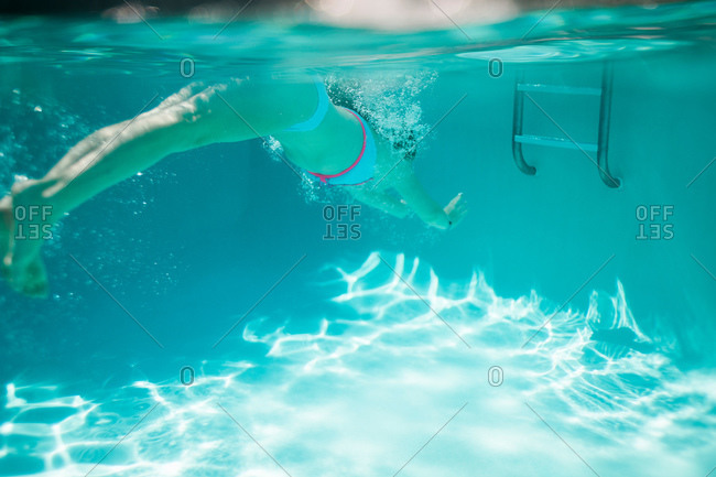 A girl swims under water to a ladder