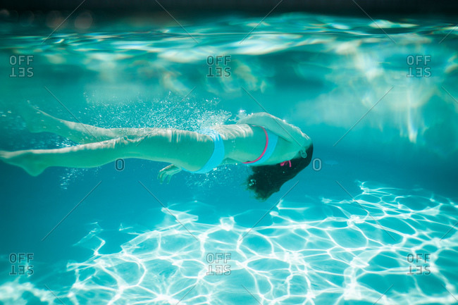 A girl swims on her back under water