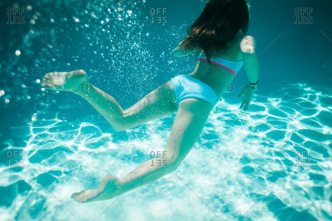 A girl swims to the surface in a pool