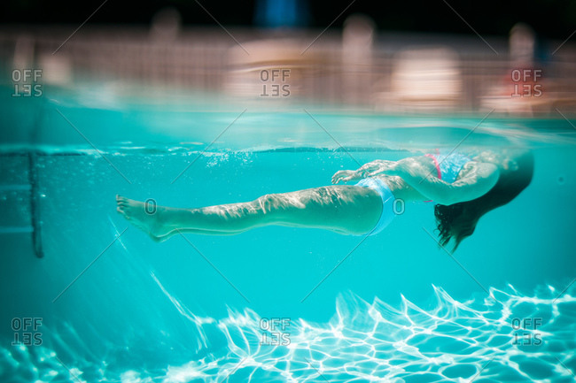 A girl floats with her head above water in a pool
