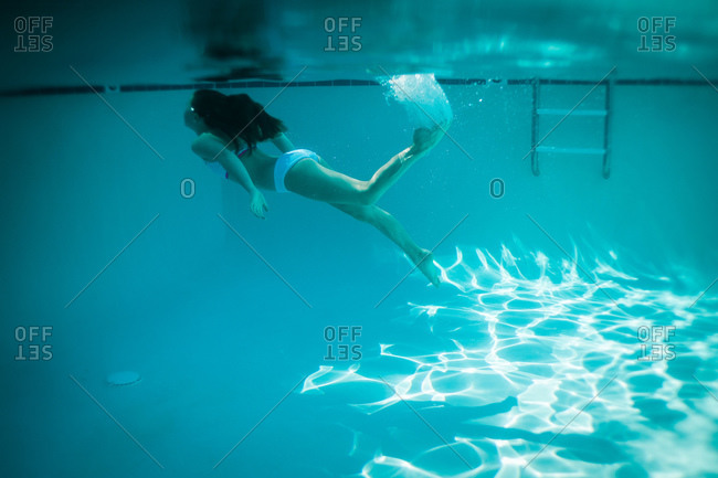 A girl swims to the edge of a pool