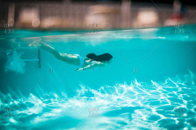 A girl swims under water at a public pool