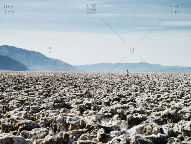 Thee people take photographs in a rocky landscape