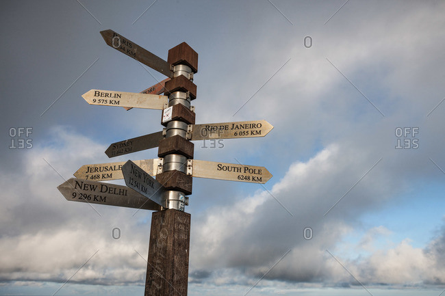 A sign post with distances to cities around the world
