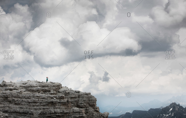 A girl stands on the top of a mountain taking a photograph
