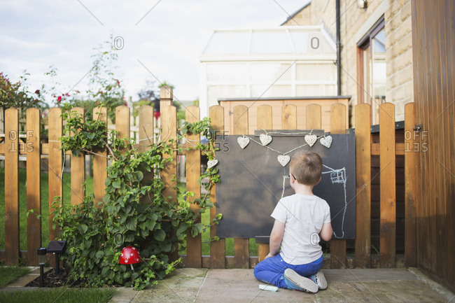 A boy draws with chalk in his yard