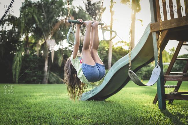 Little girl hanging from swing set bar