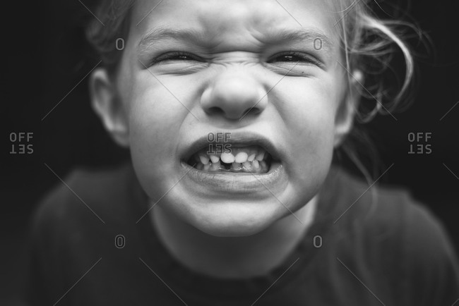 Young child making a funny face with gritted teeth