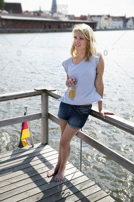 Smiling young woman with bottle of beer on a house boat