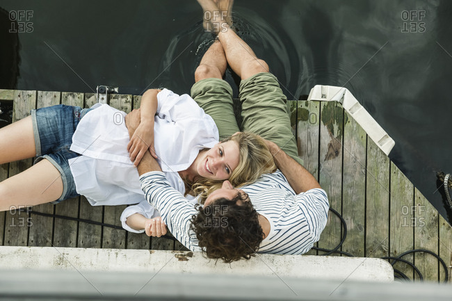 Smiling woman lying on man's lap at the water