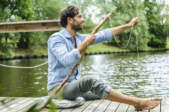 Man sitting on platform at the waterside with self-made fishing rod