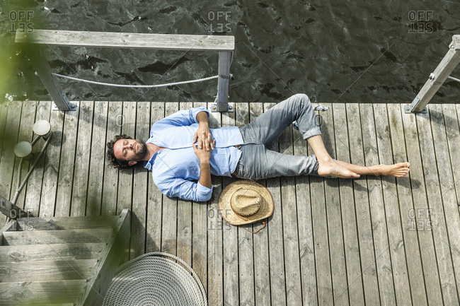Man lying on platform at the waterside